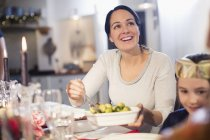 Smiling woman serving Brussels sprouts at Christmas dinner table — Stock Photo