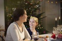 Bonne mère et fille en couronne de papier à la chandelle table de dîner de Noël — Photo de stock