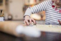 Девочка печет, используя нож для печенья — стоковое фото