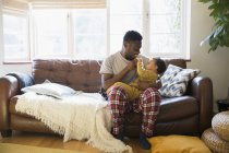 Люблячим батьком в піжамі, пригортаються дитину сина на дивані вітальні — стокове фото