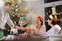 Mehrgenerationenfamilie in Pappkronen prostet Sektflöten beim Weihnachtsessen bei Kerzenschein zu — Stockfoto