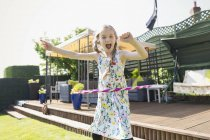 Portrait playful girl playing with plastic hoop in sunny back yard — Stock Photo
