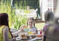 Пару лесбіянок і дочка, насолоджуючись обідом на внутрішній дворик — стокове фото