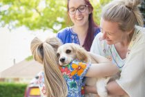 Lesbian couple and daughter hugging cute dog — Stock Photo
