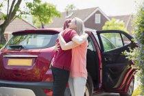 Affectueux couple lesbienne câlin en voiture dans l'allée ensoleillée — Photo de stock