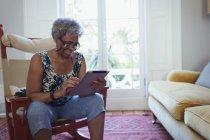 Старшая женщина, использующая цифровой планшет в гостиной — стоковое фото