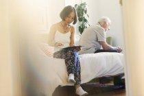 Senior couple using digital tablets in bedroom — Stock Photo