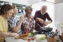 Активные старшие друзья готовят на кухне — стоковое фото