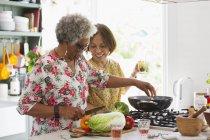 Активные пожилые женщины готовят на кухне — стоковое фото