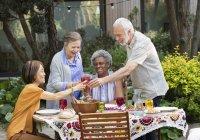 Активних старшим друзів насолоджуючись рожевих вин і обід в патіо таблиці — стокове фото