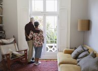 Affectionate, serene senior couple looking out living room window — Stock Photo