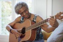 Aktive Seniorin spielt Gitarre — Stockfoto