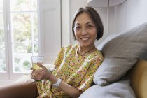 Portrait confident senior woman drinking tea in living room — Stock Photo