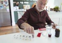 Senior man organizing pill box at kitchen table — Stock Photo
