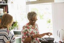 Senior women cooking at stove in kitchen — Stock Photo