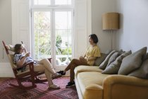 Senior women friends talking in living room — Stock Photo