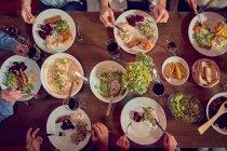 Vista desde arriba de amigos disfrutando de la cena y el vino tinto en la mesa - foto de stock
