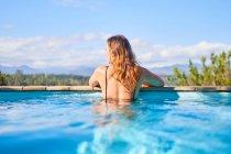 Femme sereine dans la piscine ensoleillée — Photo de stock