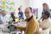 Портрет, посміхаючись, впевнено активних старшим людина, насолоджуючись квітка організацію класу — стокове фото