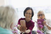 Aktive Frauen in Führungspositionen mit Handykamera fotografiert Orchideen im Blumenbinden Klasse — Stockfoto