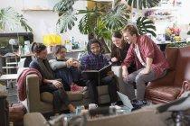 Молодой взрослый сосед друзей, читать книги в гостиной квартиры — стоковое фото