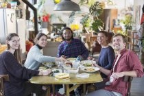 Portrait smiling, confident young adult roommate friends enjoying lunch at apartment table — Stock Photo