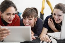 Laughing young women friends hanging out, enjoying digital tablet and laptop on bed — Stock Photo