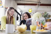 Young women roommate friends at kitchen table — Stock Photo