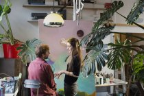 Художники, обсуждая живописи в квартире — стоковое фото