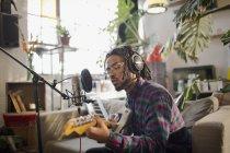 Jovem músico masculino gravação de música, tocando guitarra no microfone no apartamento — Fotografia de Stock