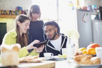 Young adult roommate friends using smart phone at breakfast table in apartment — Stock Photo