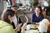 Amigos de joven compañero adultos disfrutar de un desayuno en la mesa de la cocina de apartamento - foto de stock