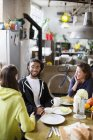 Young adult roommate friends talking at breakfast table in apartment — Stock Photo