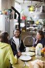Amis de jeunes adultes colocataire parler à la table du petit déjeuner dans l'appartement — Photo de stock