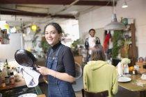 Портрет улыбающийся молодой женщины, мыть посуду в квартире — стоковое фото
