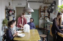 Amigos del compañero adulto joven preparándose para comer comida para llevar en la cocina - foto de stock