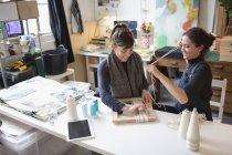 Jeunes femmes amis assemblant le cadre photo de corde — Photo de stock