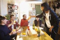 Jeunes adultes amis dégustant cocktails à la table de cuisine appartement — Photo de stock