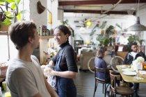 Amigos do jovem colega fazendo pratos e falando em cozinha de apartamento — Fotografia de Stock