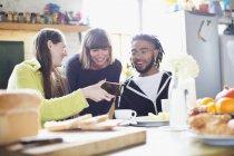 Jungen Mitbewohner Freunde mit Smartphone am Frühstückstisch in Wohnung — Stockfoto
