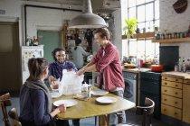 Jungen Mitbewohner Freunde Take Away Essen am Küchentisch in Wohnung vorbereiten — Stockfoto