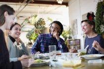 Молодой сосед друзьями, наслаждаясь вынос пищи на кухне в квартире — стоковое фото