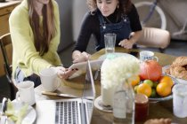 Young women roommate friends using digital tablet at breakfast table — Stock Photo
