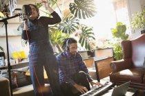 Giovane uomo e donna registrazione musica, cantare e suonare il pianoforte in appartamento — Foto stock