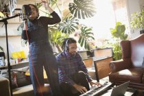 Young man and woman recording music, singing and playing piano in apartment — Stock Photo