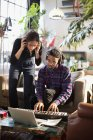 Young man and woman recording music, playing keyboard piano in apartment — Stock Photo