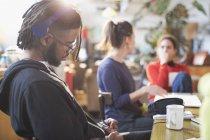 Giovane con le cuffie che studia al tavolo della cucina — Foto stock
