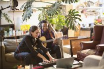 Young man and woman recording music, playing guitar and keyboard piano in apartment — Stock Photo