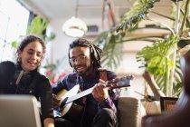 Giovane e donna registrazione di musica, suonare la chitarra in appartamento — Foto stock