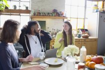 Young college student roommate friends studying at breakfast table — Stock Photo